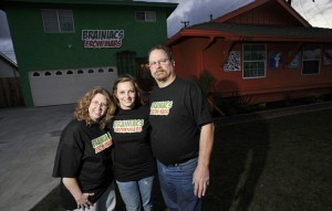 Sarah Hostetler (C) and her parents Beth and Scott pose in front of their home in Buena Park, California